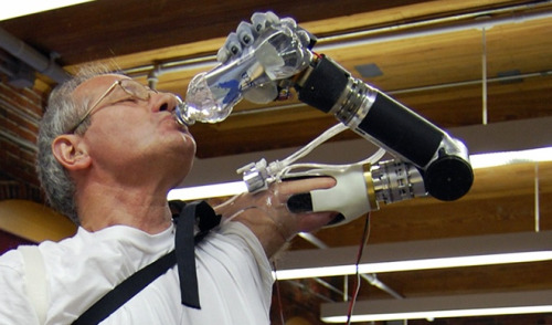man drinking water with bionic arm